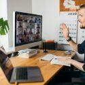 Giovane professionista biondo alla scrivania lavorando da casa e partecipando a una riunione